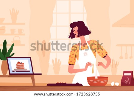 A young woman watches a recipe video on a laptop and prepares pancakes at home in the kitchen at home. The concept of home cooking and search for a recipe on the Internet