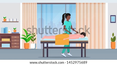 african american acupuncturist holding needle man patient getting acupuncture treatment treatments alternative medicine concept modern spa salon interior full length horizontal