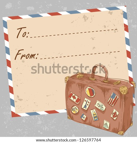 Air mail travel postcard with old grunge envelope and suitcase covered with stickers from different countries