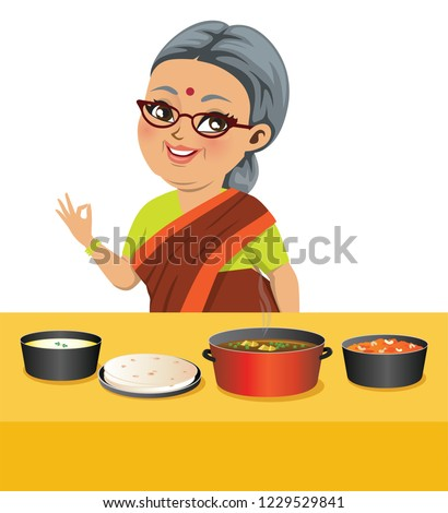 An Indian fat old grandmother wearing a saree has just cooked wholesome Indian food with spicy curried veggies, roti (Indian flat bread) and halwa or sweet carrot pudding.
