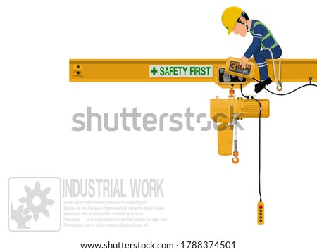 An industrial worker is repairing electric chain hoist