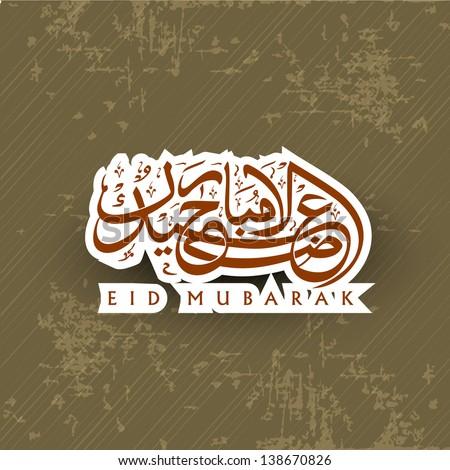 Arabic Islamic Calligraphy of shiny text Eid Mubarak on grungy brown background.