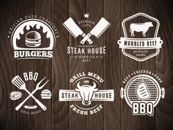 BBQ, burger, grill badges. Set of vector barbecue logos. Retro emblems for steak house or grill bar on vintage wooden background.