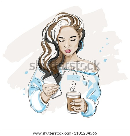 Beautiful woman holding a phone and a cup of coffee