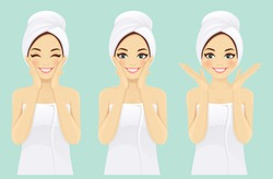 Beautiful young woman in towel with clean fresh skin touch own face