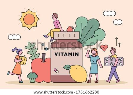Big vitamin barrels and fresh vegetables. Small people stand around vitamins. flat design style minimal vector illustration.