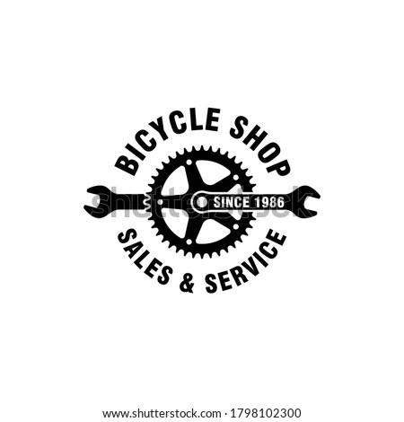 Black and white illustration of a wrench, bicycle gear, text on a white background. Vector illustration advertises the sale and service of bicycles. Bicycle shop logo.