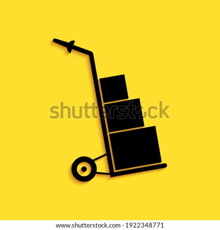 Black Hand truck and boxes icon isolated on yellow background. Dolly symbol. Long shadow style. Vector. Stock photo ©