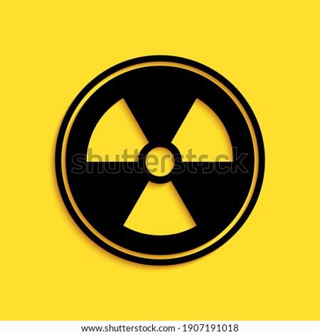 Black Radioactive icon isolated on yellow background. Radioactive toxic symbol. Radiation Hazard sign. Long shadow style. Vector. Сток-фото ©