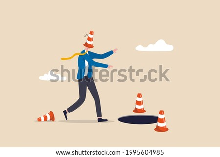 Blind and frustrated business direction, mistake or failure, trap or crisis ahead, risk and uncertainty concept, blindfold businessman cover with pylon walking to fall into the hole or business trap. Foto stock ©