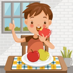 Boy eating apple.sitting at the table  eating fruit.Red apple biting.green apple in a tray placed on a table at home in the dining room.emotional mood on child's face feels good.Symbols hand thumb up.