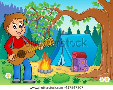 boy guitar player in campsite