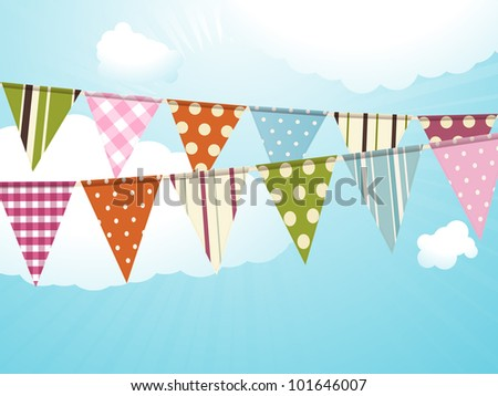 Bunting against a blue sky with fluffy clouds
