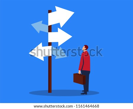 Businessman looking at complicated road sign