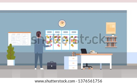 businessman scheduling his work agenda weekly meeting schedule task board with sticky notes business planning news events timetable concept office interior horizontal full length flat