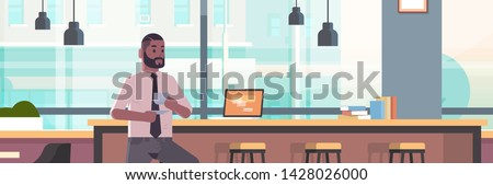 businessman sitting on chair at bar counter with laptop coffee break concept african american business man drinking cappuccino modern cafe interior flat portrait horizontal