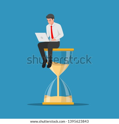 Businessman working with laptop sitting on big hourglass. Time management and deadline concept