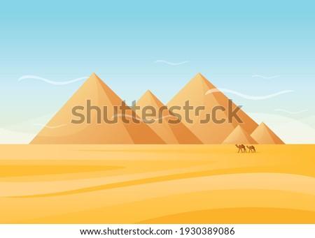Caravan of camels near Egypt pyramids landscape. Egyptian great pyramids in the desert on a background. Dry desert under sun, endless sand desert.