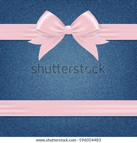 Card with pink gift bow and ribbon on denim background.