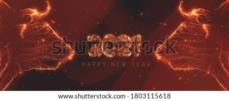 Chinese new year 2021 year of the ox. Bull heads made with glowing lines and sparks. 2021 Happy New Year text made with spark trails. Golden magical greeting card.