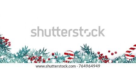 christmas border or frame with fir branches berries and candy isolated on snowy background