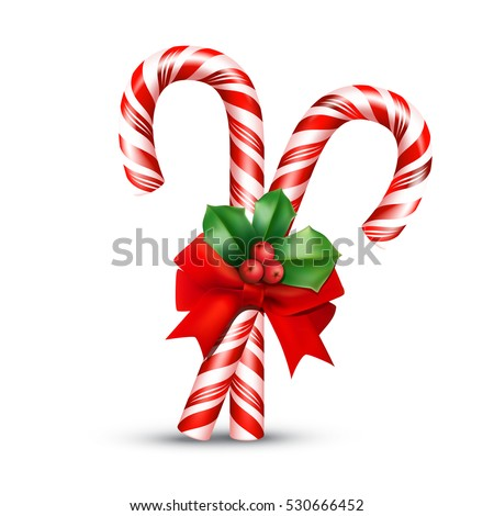 Christmas candy cane with red bow and holly berries isolated on white background.