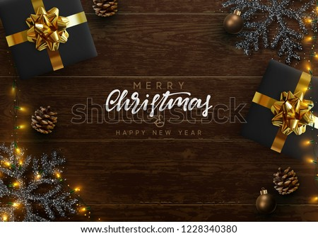 Christmas composition on wooden background. Xmas decoration design, box gift, snowflake color black, gold light garland, pine cone. Brown realistic wood texture. Flat lay, top view.