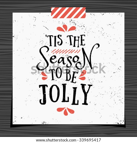 Christmas typographic design greeting card template. 'Tis the Season to be Jolly message in black and red on white background. Christmas card with a strip of washi tape on dark wood background.