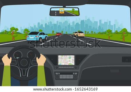 City traffic on the highway with car dashboard and panoramic view on modern city with skyscrapers and suburbs on background mountains, hills. Road with cars leading to city.