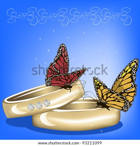 Closeup of two rings with butterflies on blue background.