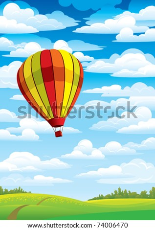 Colored balloon on a blue sky, white clouds and green meadow