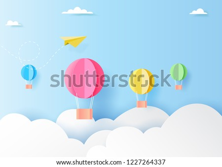 Colorful hot air balloons and yellow paper airplane flying on clouds and blue sky paper art style.Vector illustration.
