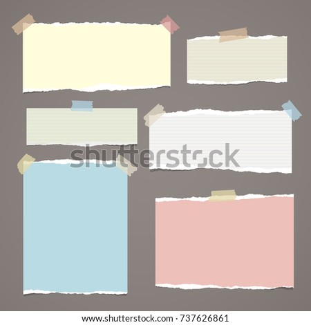 Colorful ripped paper strips, notebook sheets for note or message stuck with sticky tape on dark brown background.