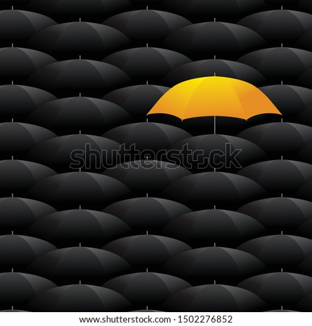 Concept of individuality and difference. Yellow umbrella among many dark ones. Standing out from crowd