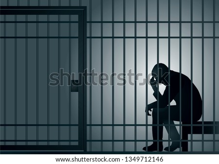 Concept of the prison with the arrest of a criminal. The prisoner is sitting in his cell and desperate, holding his head in his hands.