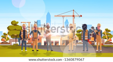 construction workers team industrial technicians builders group over city construction site tower cranes building residential buildings cityscape background flat horizontal full length