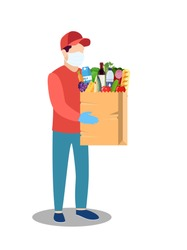 COVID-19. Quarantine in the city. Coronavirus epidemic. Courier man in a protective medical mask holds bag full of groceries products in his hands. Free food delivery. Stay home