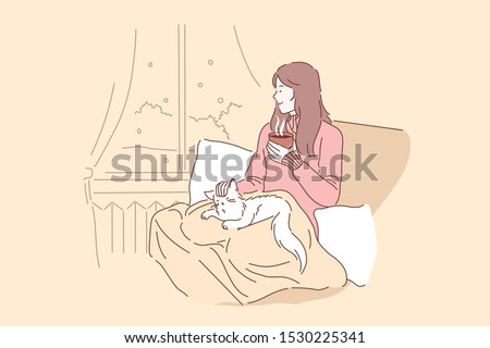 Cozy, relax, dream concept. Young woman or girl enjoys the comfort of sitting on a chair with a blanket and caressing her pet cat. Thoughtful lady in looks out the window and drinks tea or coffee.
