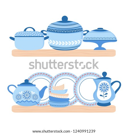 Crockery ceramic cookware. Blue porcelain bowls, plates, teapot and pand on the wood shelfs