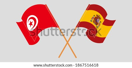 Crossed and waving flags of Tunisia and Spain