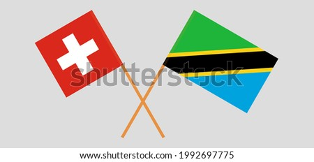 Crossed flags of Switzerland and Tanzania. Official colors. Correct proportion