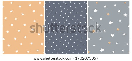 Cute Abstract Starry Sky Seamless Vector Patterns. White Freehand Stars on a Gray, Graphite and Pale Orange Background. Simple Infantile Style Irregular Print with Funny Hand Drawn Stars. Stockfoto ©
