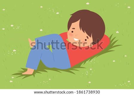 Cute Boy Lying Down on Green Lawn, Kid Lying on Grass Dreamily Looking into Sky Cartoon Vector Illustration Foto d'archivio ©