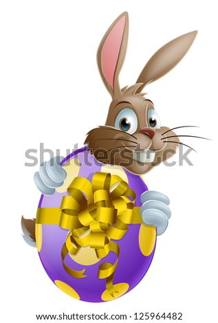 Cute Easter bunny cartoon character holding onto and peeking round a painted chocolate Easter egg - stock vector