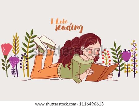 Cute little girl reading a book in the garden