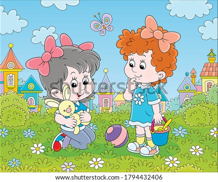 Cute little girls playing with a small toy rabbit among flowers on green grass of a lawn against a background of colorful houses of a small town, vector cartoon illustration Stock photo ©