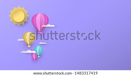Cute papercut copy space illustration of hot air balloons in pastel color sky with sun and clouds. Children nursery background or imagination concept.