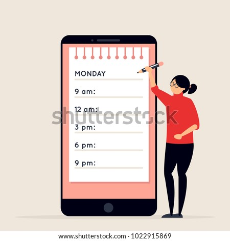 Day planning and scheduling concept. Young woman with pencil standing next to big smartphone with calendar on its screen. Girl making notes in planner app. Time organizer