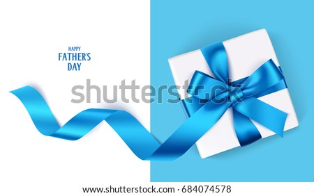 Decorative gift box with blue bow and long ribbon. Happy Father's Day text. Top view