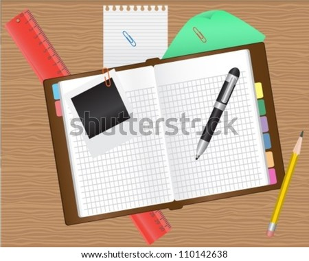 diary and office supplies on a wooden table